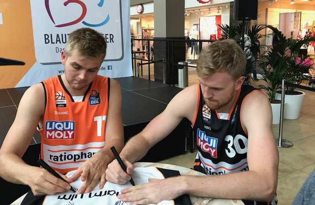 Till Pape und Maximilian Ugrai unterschreiben auf einem Trikot.